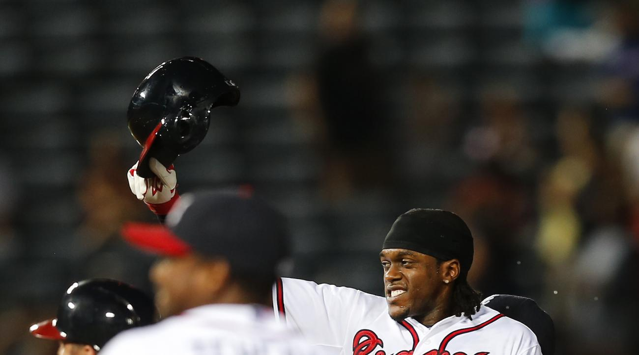 Atlanta Braves' Cameron Maybin (25) celebrates after driving in the game-winning run with a base hit in the ninth inning of a baseball game against the Washington Nationals on Thursday, July 2, 2015, in Atlanta. Atlanta won 2-1. (AP Photo/John Bazemore)
