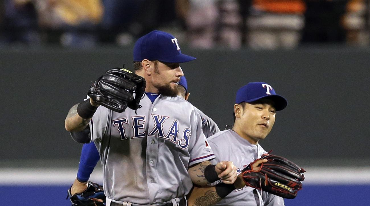 Texas Rangers outfielders Josh Hamilton, left, Shin-Soo Choo, and Leonys Martin celebrate after a baseball game against the Baltimore Orioles, Thursday, July 2, 2015, in Baltimore. Texas won 2-0. (AP Photo/Patrick Semansky)