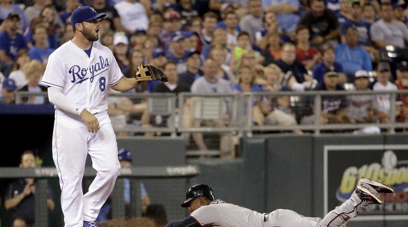 Minnesota Twins' Eduardo Escobar slides in with an RBI triple as Kansas City Royals third baseman Mike Moustakas waits for the ball during the ninth inning of a baseball game against the Kansas City Royals Thursday, July 2, 2015, in Kansas City, Mo. (AP P