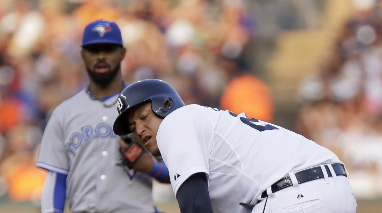 Detroit Tigers' Miguel Cabrera grabs his left leg after a steal attempt during the fourth inning as Toronto Blue Jays' Jose Reyes looks on during a baseball game Friday, July 3, 2015, in Detroit. Cabrera left the game with a strained left calf. (AP Photo/