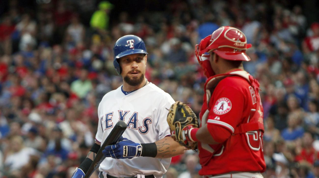 Texas Rangers' Josh Hamilton comes to the plate and talks with Los Angeles Angels catcher Carlos Perez (58) in the second inning of a baseball game in Arlington, Texas on Friday, July 3, 2015. (AP Photo/Brad Loper)