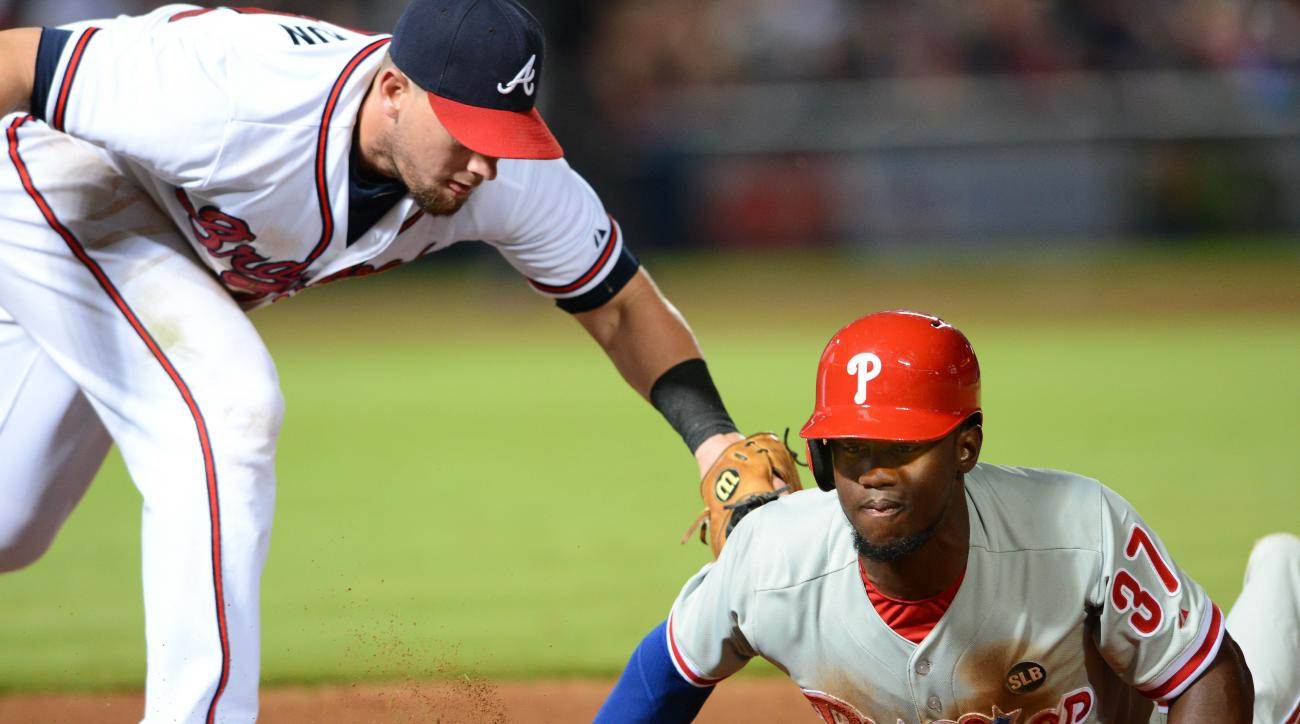 Philadelphia Phillies center fielder Odubel Herrera is safe diving back to first base on a pick-off attempt as Atlanta Braves first baseman Chris Johnson applies the tag during the seventh inning of a baseball game Friday, July 3, 2015, in Atlanta. (AP Ph