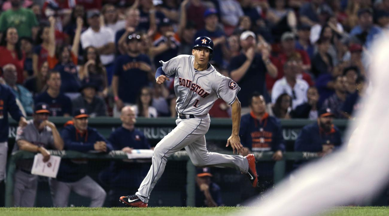 Houston Astros' Carlos Correa heads home as he scores on a two-run single by Jon Singleton during the 10th inning of a baseball game against the Boston Red Sox at Fenway Park in Boston, Friday July 3, 2015. (AP Photo/Charles Krupa)