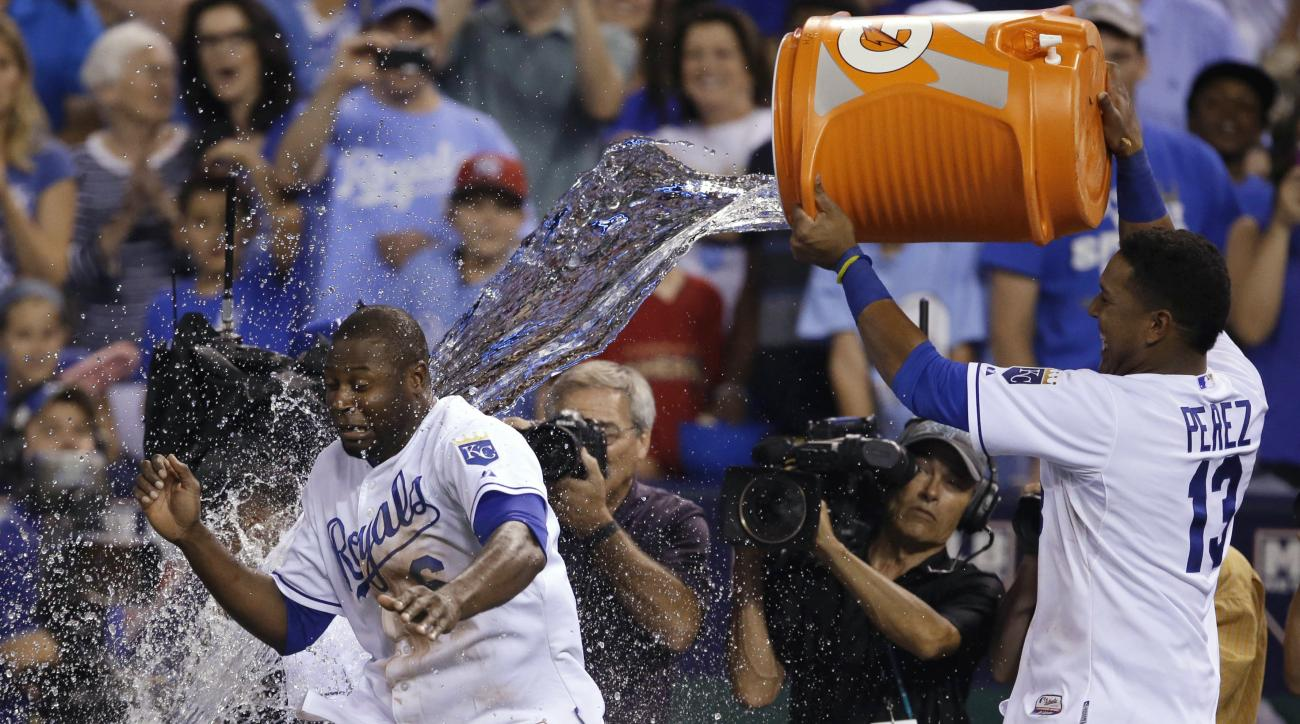 Kansas City Royals' Lorenzo Cain, left, tries to dodge a cooler of water being emptied by teammate Salvador Perez (13) following a baseball game against the Minnesota Twins at Kauffman Stadium in Kansas City, Mo., Friday, July 3, 2015. Cain scored the win