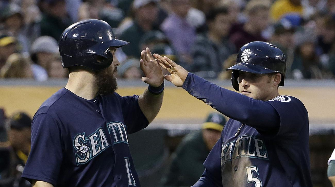 Seattle Mariners' Brad Miller, right, celebrates after hitting a two-run home run that scored Dustin Ackley, left, during the eighth inning of a baseball game against the Oakland Athletics in Oakland, Calif., Friday, July 3, 2015. (AP Photo/Jeff Chiu)