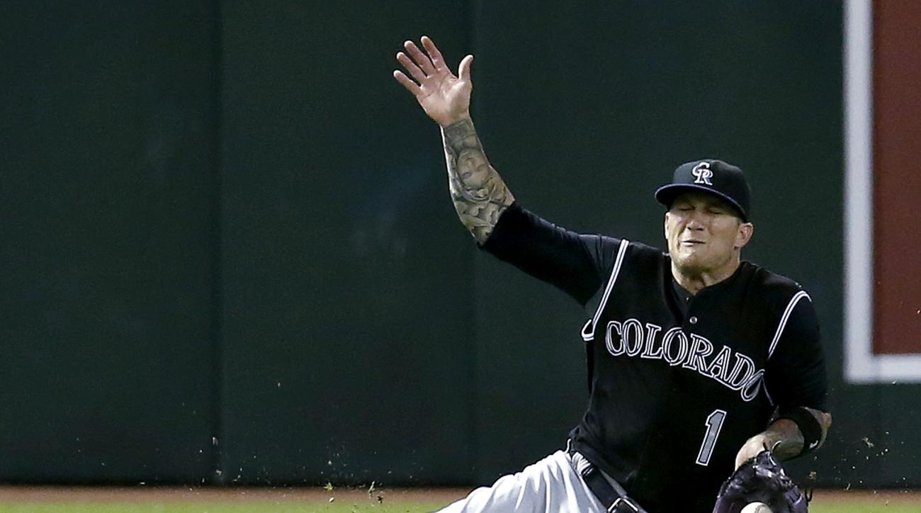 Colorado Rockies left fielder Brandon Barnes cannot make the catch on a ball hit by Arizona Diamondbacks' Jake Lamb during the sixth inning of a baseball game, Friday, July 3, 2015, in Phoenix. (AP Photo/Rick Scuteri)