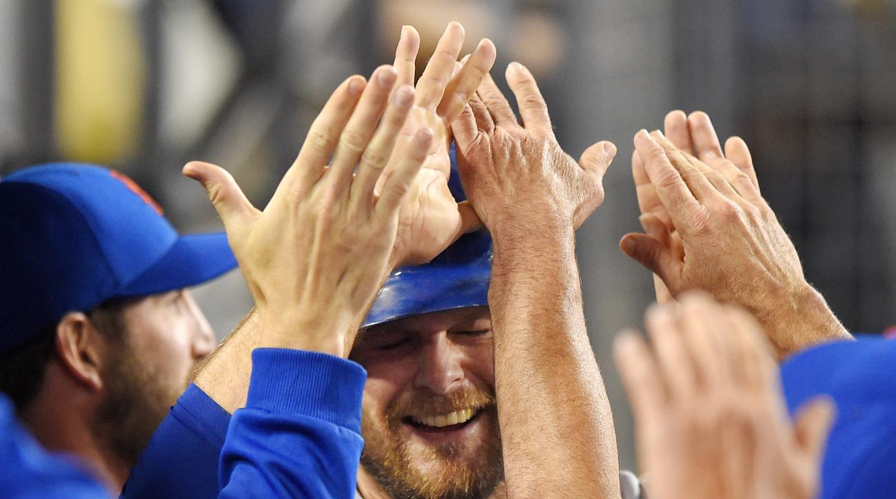 New York Mets' Lucas Duda is congratulated in the dugout by teammates after scoring on sacrifice fly by Kevin Plawecki during the ninth inning of a baseball game against the Los Angeles Dodgers, Friday, July 3, 2015, in Los Angeles. The Mets won 2-1. (AP