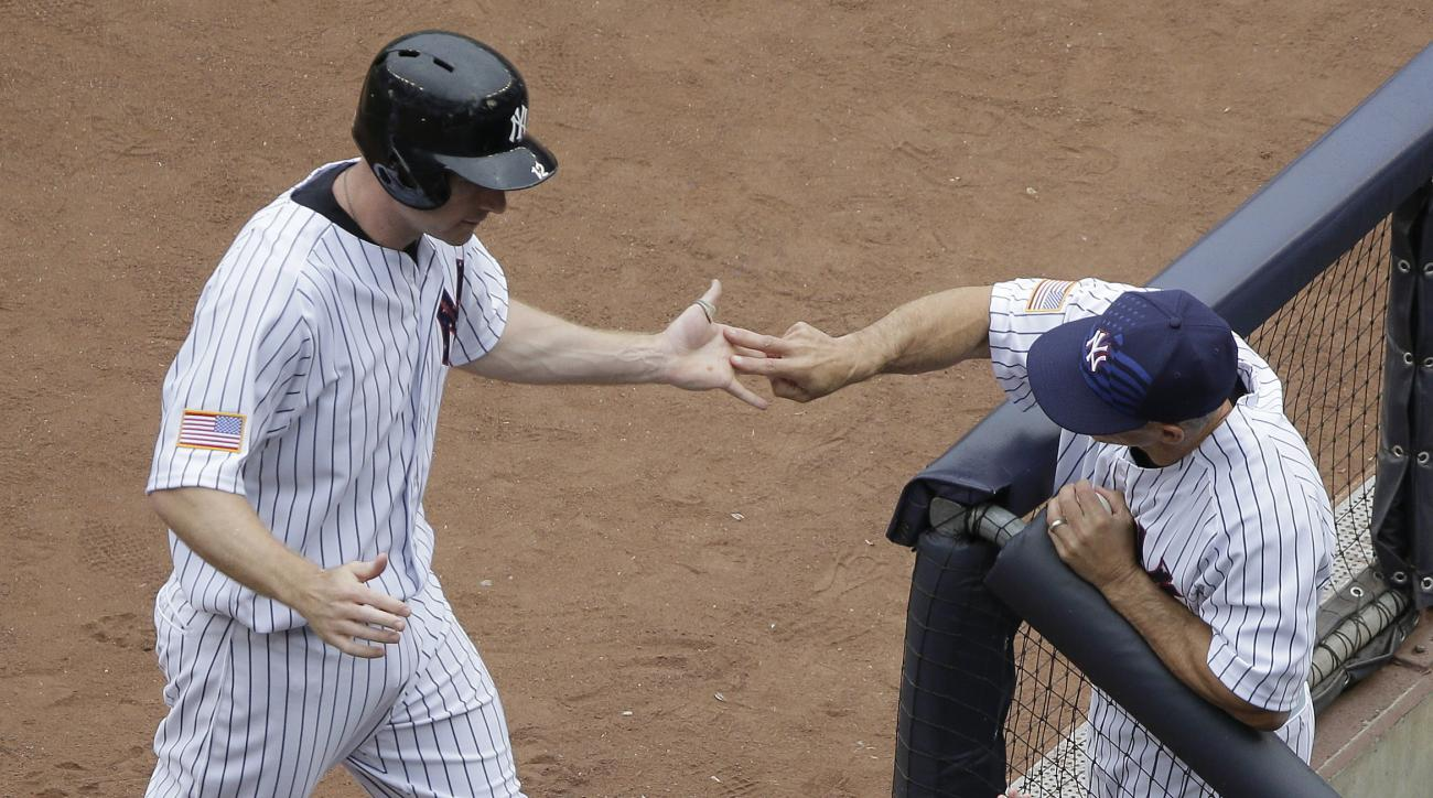 New York Yankees Chase Headley, left, is greeted by manager Joe Girardi after scoring against the Tampa Bay Rays during the first inning of a baseball game, Saturday, July 4, 2015, in New York. (AP Photo/Julie Jacobson)