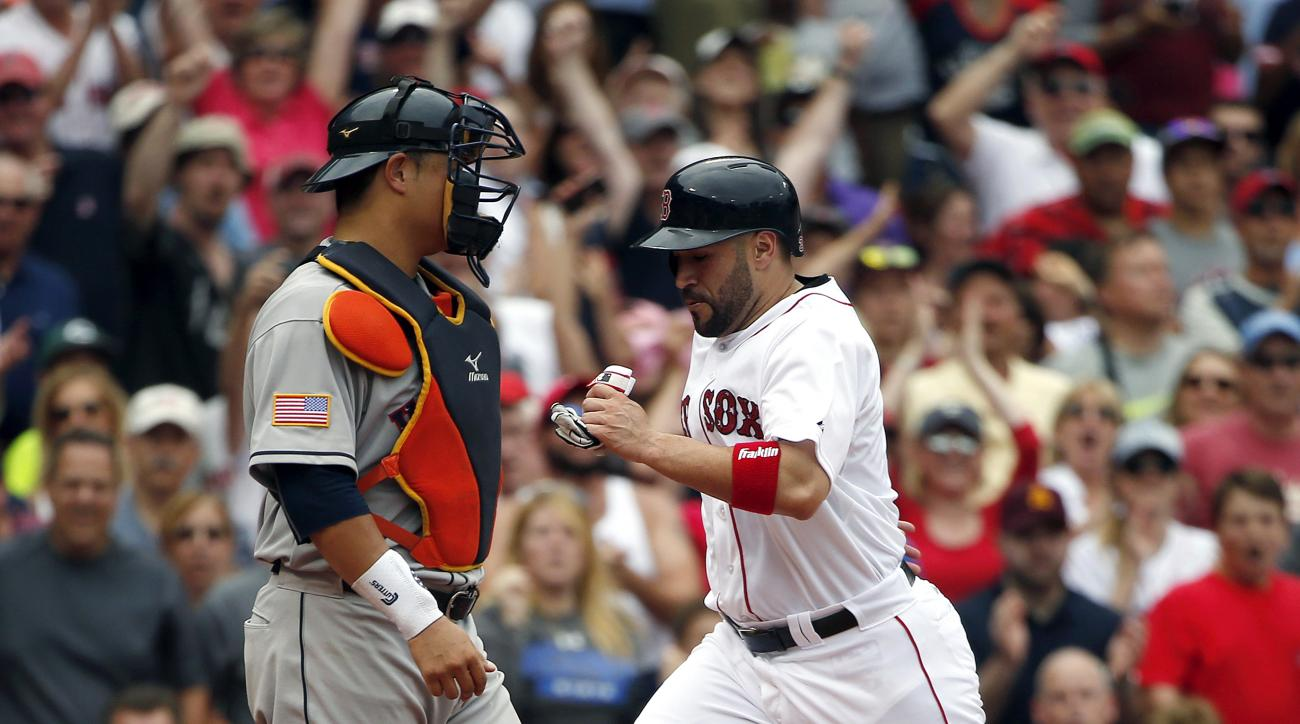 Boston Red Sox's Sandy Leon, right, scores in front of Houston Astros' Hank Conger on a double by Mookie Betts during the sixth inning of a baseball game in Boston, Saturday, July 4, 2015. (AP Photo/Michael Dwyer)