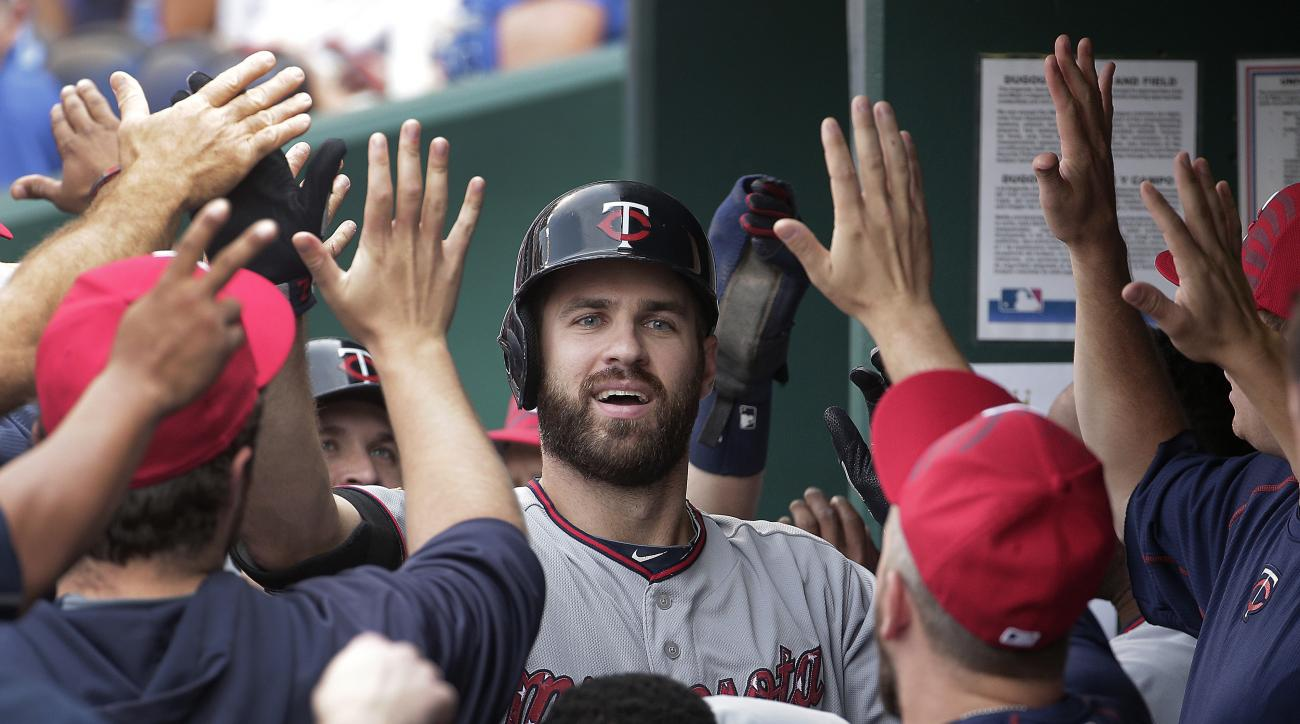 Minnesota Twins' Joe Mauer (7) celebrates in the dugout after his two-run home run during the first inning of a baseball game against the Kansas City Royals on Saturday, July 4, 2015, in Kansas City, Mo. (AP Photo/Charlie Riedel)