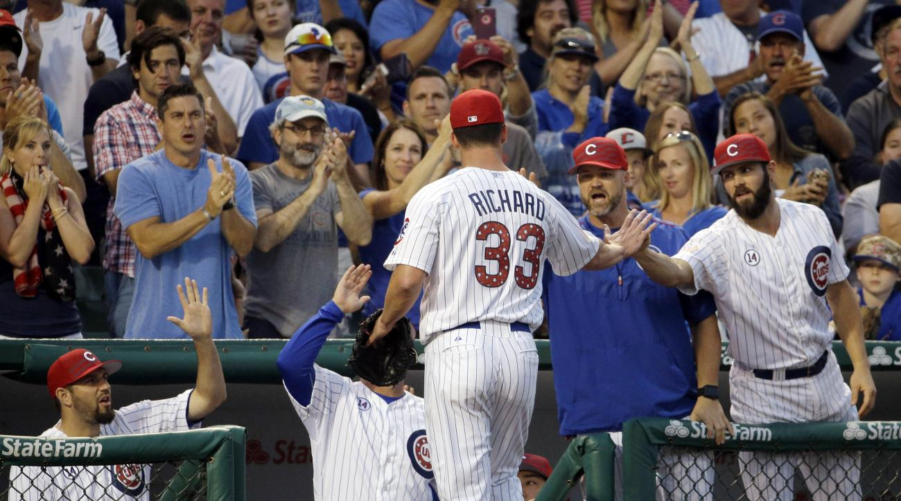 Chicago Cubs starter Clayton Richard (33) celebrates with teammates as he leaves the field during the seventh inning of a baseball game against the Miami Marlins, Saturday, July 4, 2015, in Chicago. (AP Photo/Nam Y. Huh)