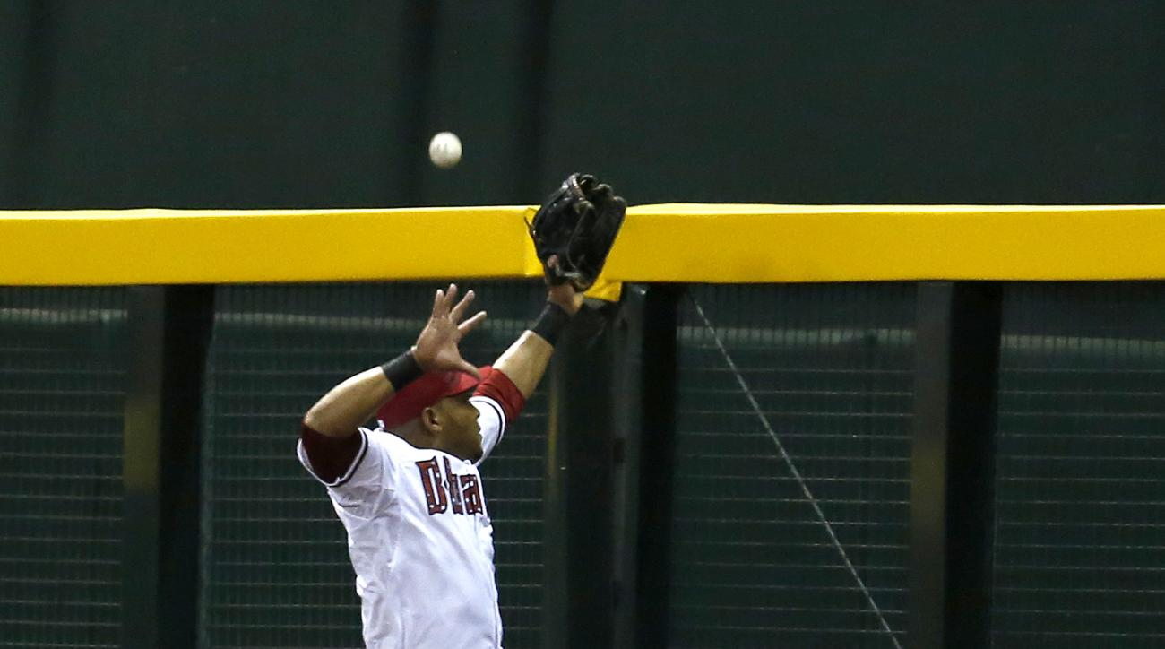 Arizona Diamondbacks right fielder Yasmany Tomas jumps for a triple by Colorado Rockies' Nick Hundley during the fourth inning during a baseball game, Saturday, July 4, 2015, in Phoenix. (AP Photo/Rick Scuteri)
