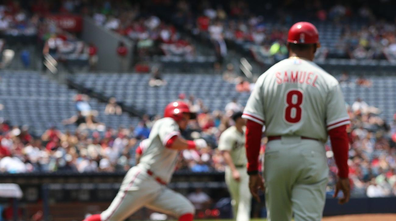 A pair of birds work the ball field looking for a snack as Phillies Freddy Galvis trys to beat out a ground ball unsuccessfully against the Braves during the 6th inning in a baseball game on Sunday, July 5, 2015, in Atlanta.  First Base Coach Juan Samuel(