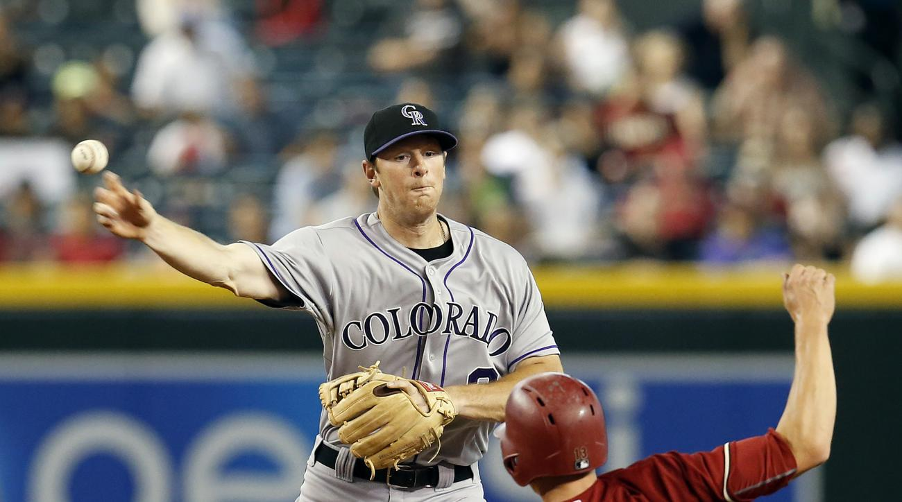 Colorado Rockies second baseman DJ LeMahieu, left, turns the double play while avoiding Arizona Diamondbacks Nick Ahmed (13) on a ball hit by A.J. Pollock in the third inning during a baseball game, Sunday, July 5, 2015, in Phoenix. (AP Photo/Rick Scuteri