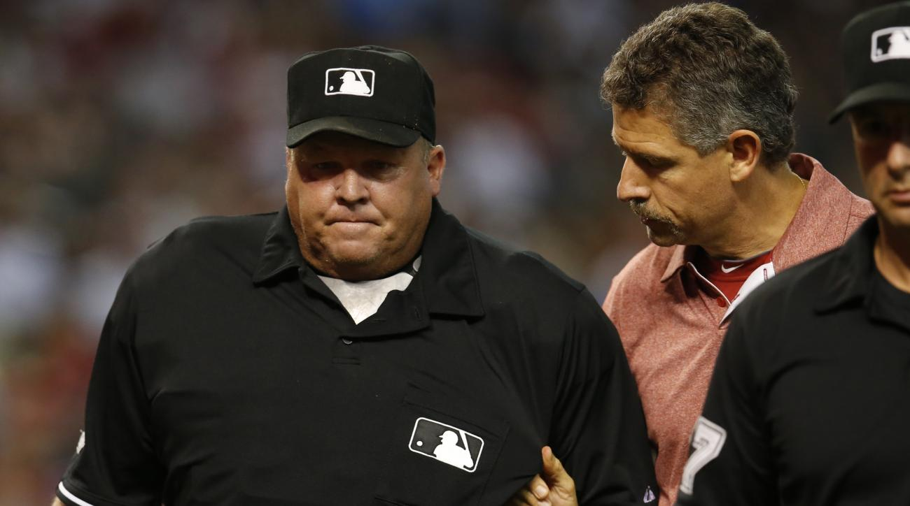 Umpire Fieldin Culbreth, left, is helped off the field by Arizona Diamondbacks trainer Ken Credshaw in the second inning during a baseball game against the Colorado Rockies, Sunday, July 5, 2015, in Phoenix. Culbreth had to leave the game after being hit