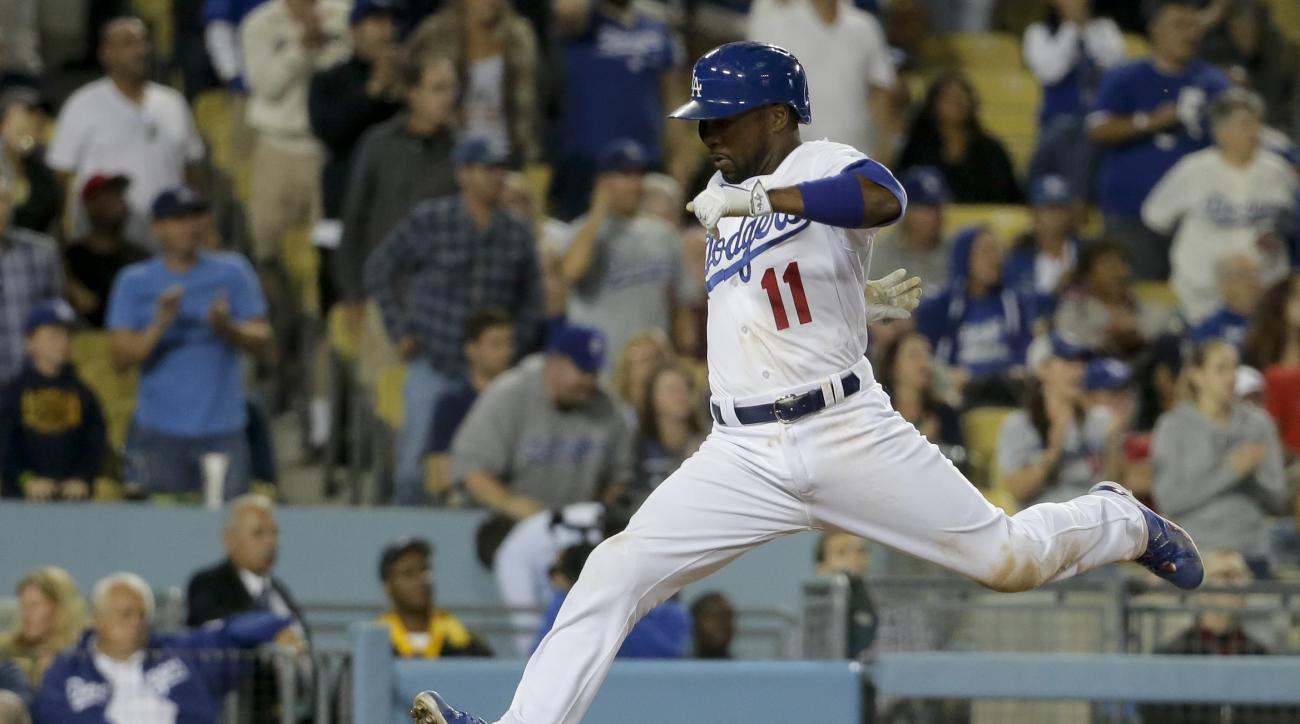Los Angeles Dodgers' Jimmy Rollins scores on a double by Joc Pederson against the Philadelphia Phillies during the seventh inning of a baseball game in Los Angeles, Monday, July 6, 2015. (AP Photo/Chris Carlson)