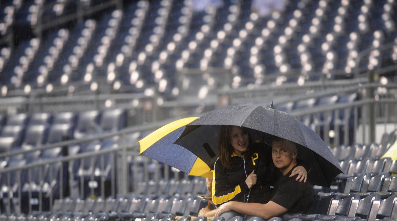 Cathy McConnell and Josh McConnell stay dry during a rain delay at a baseball game between the Pittsburgh Pirates and the San Diego Padres in Pittsburgh, Tuesday, July 7, 2015. (AP Photo/Vincent Pugliese)