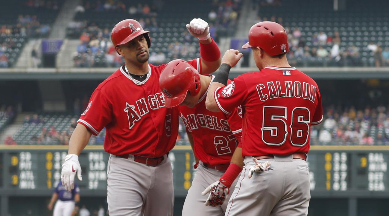 Los Angeles Angels' Albert Pujols, left, is congratulated after hitting a three-run home run by teammates Mike Trout, center, and Kole Calhoun against the Colorado Rockies in the first inning of an inter league baseball game Tuesday, July 7, 2015, in Denv