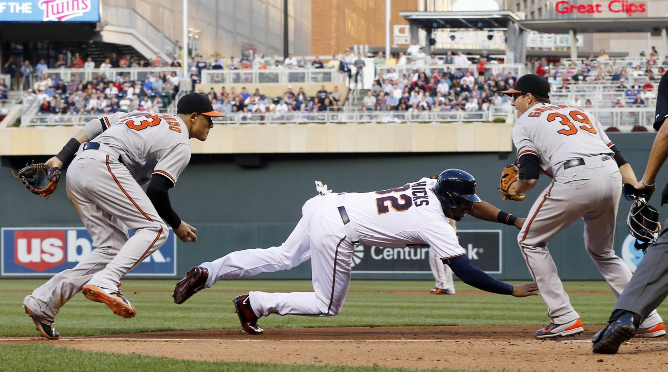 Minnesota Twins' Aaron Hicks, center, hits the ground after being tagged in a rundown by Baltimore Orioles third baseman Manny Machado, left, in the fourth inning of a baseball game, Tuesday, July 7, 2015, in Minneapolis.AT right is catcher Matt Wieters.