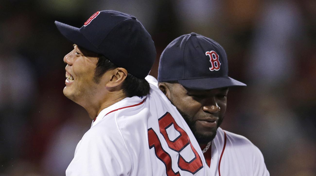 Boston Red Sox relief pitcher Koji Uehara is embraced by David Ortiz after the final out of a baseball game against the Miami Marlins at Fenway Park in Boston, Tuesday July 7, 2015. Uehara earned a save in the Red Sox 4-3 win. (AP Photo/Charles Krupa)