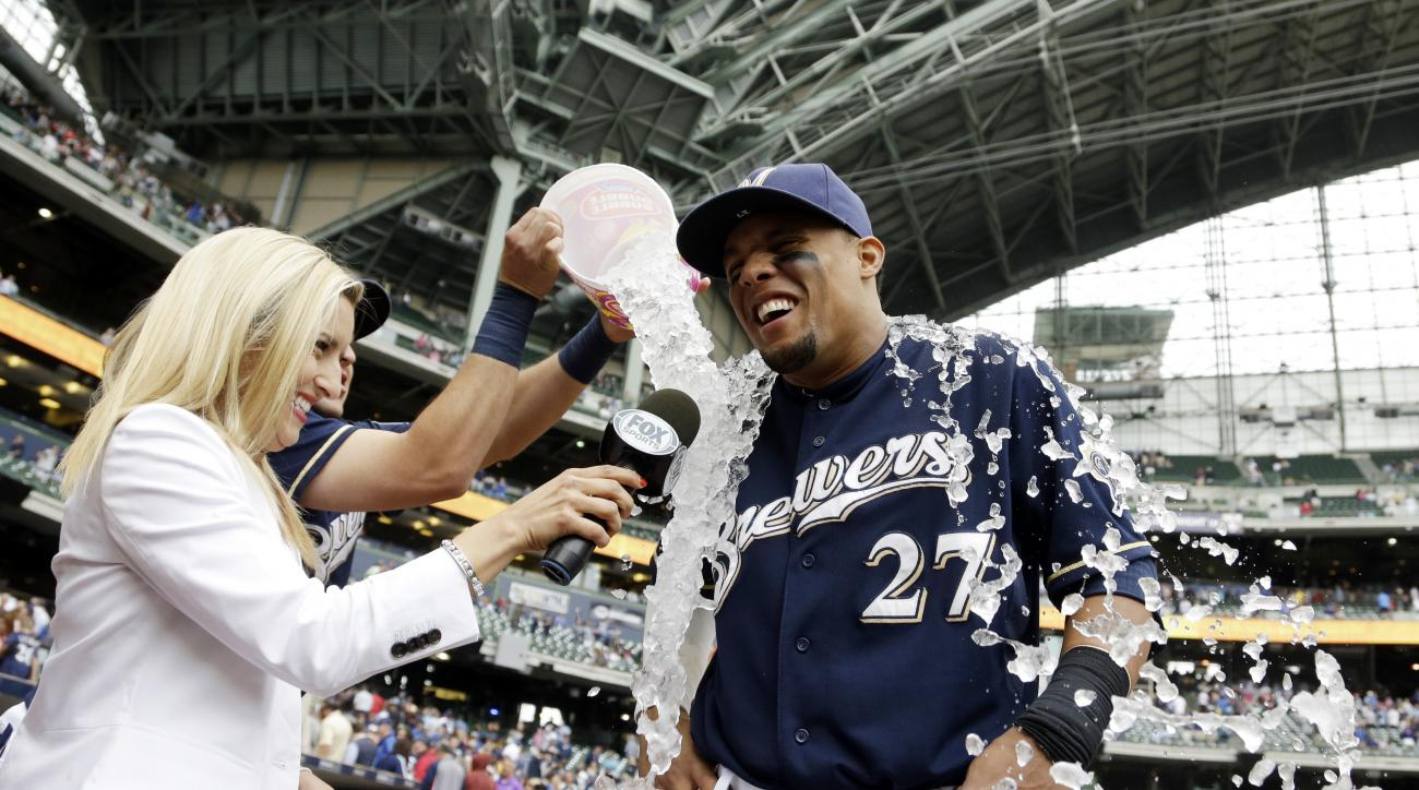 Milwaukee Brewers' Carlos Gomez is dunked by teammate Hernan Perez during a TV interview after a baseball game against the Atlanta Braves Wednesday, July 8, 2015, in Milwaukee. The Brewers won 6-5. (AP Photo/Morry Gash)