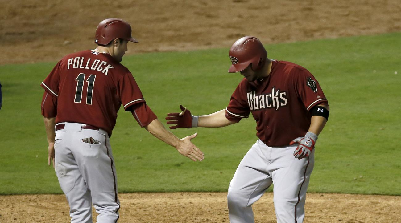 Arizona Diamondbacks' A.J. Pollock (11) and Welington Castillo celebrate at home plate after Castillo hit a two-run home run that scored Pollock in the fifth inning of an interleague baseball game against the Texas Rangers Wednesday, July 8, 2015, in Arli