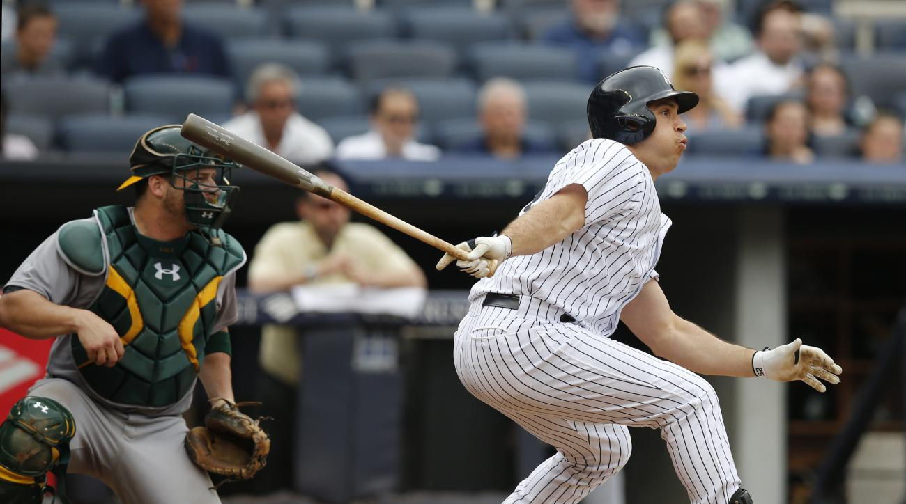 New York Yankees designated hitter Mark Teixeira hits a third-inning, RBI single in a baseball game against the Oakland Athletics at Yankee Stadium in New York, Thursday, July 9, 2015.  (AP Photo/Kathy Willens)