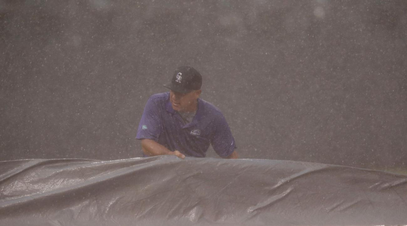 Head groundskeeper Mark Razum struggles to pull the tarp during a heavy rainfall in the bottom of the first inning of the Colorado Rockies' baseball game Atlanta Braves on Thursday, July 9, 2015, in Denver. (AP Photo/David Zalubowski)