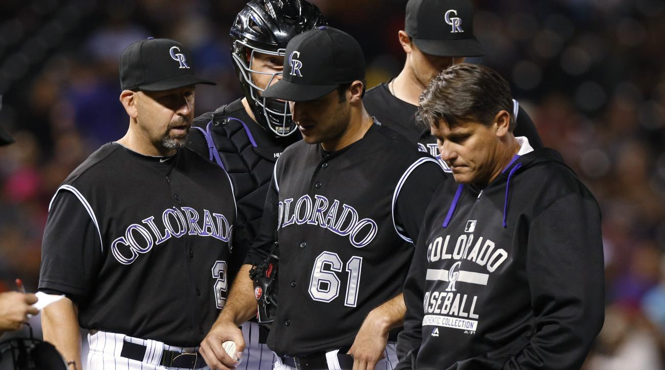 Colorado Rockies manager Walt Weiss, left, watches as relief pitcher David Hale, center, is escorted off the mound by head trainer Keith Dugger during the third inning of a baseball game against the Atlanta Braves on Thursday, July 9, 2015, in Denver. (AP
