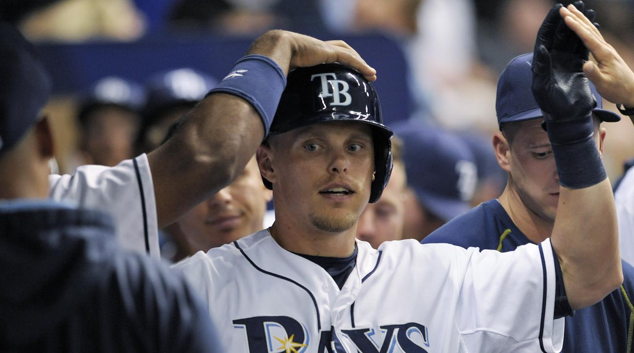 Tampa Bay Rays teammates greet Brandon Guyer in the dugout after his solo home run off Houston Astros starter Collin McHugh during the seventh inning of a baseball game Friday, July 10, 2015, in St. Petersburg, Fla. (AP Photo/Steve Nesius)