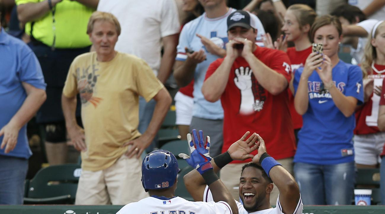 Texas Rangers' Adrian Beltre (29) is greeted at the top of the dugout by Elvis Andrus, right, and bench coach Steve Buechele, bottom left, after Beltre hit a solo home run off of San Diego Padres starting pitcher Ian Kennedy during the fourth inning of an