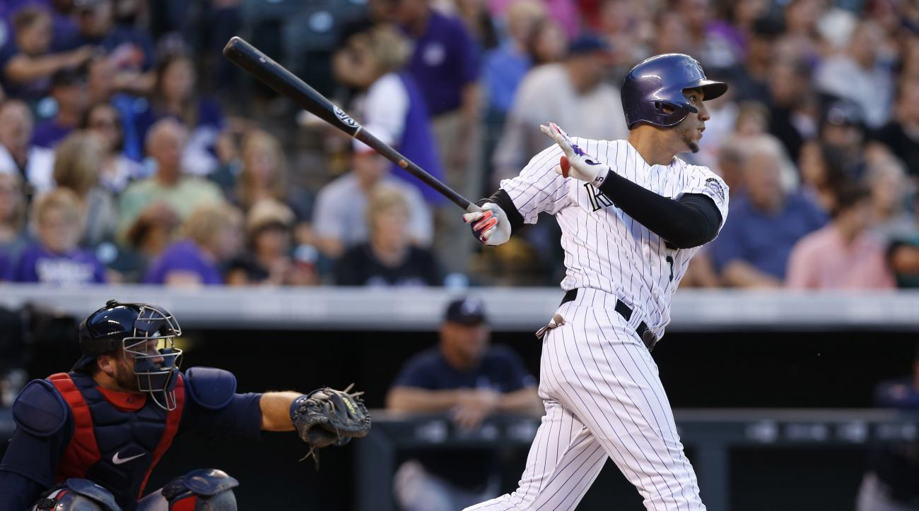 Colorado Rockies Carlos Gonzalez, right, follows the flight of his solo home run with Atlanta Braves catcher A.J. Pierzynski in the fifth inning of a baseball game Friday, July 10, 2015, in Denver. (AP Photo/David Zalubowski)
