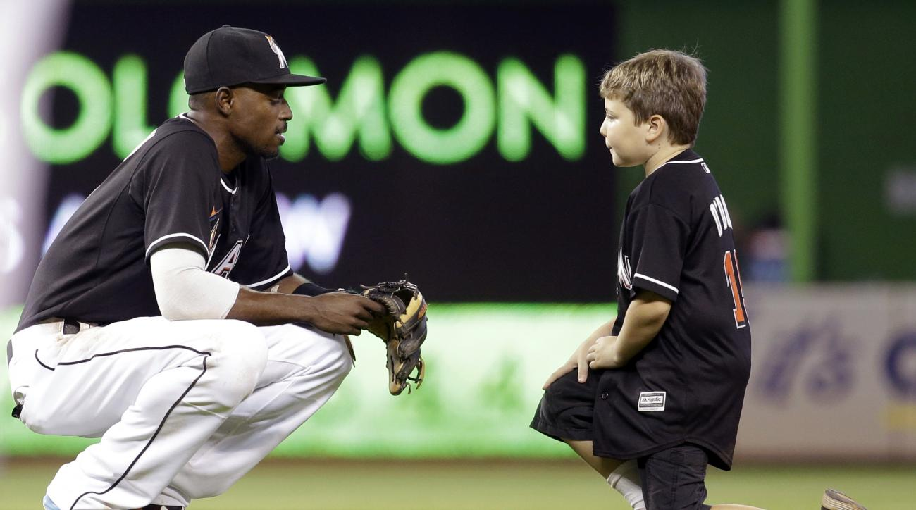 Miami Marlins second baseman Dee Gordon, left, talks with Matthew Odowd, 8, between innings during a baseball game against the Cincinnati Reds, Saturday, July 11, 2015, in Miami. (AP Photo/Lynne Sladky)