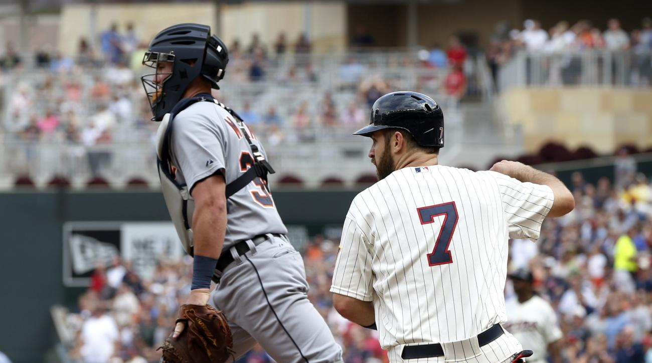 Minnesota Twins' Joe Mauer, right, watches after scoring on a double by Miguel Sano, next to Detroit Tigers catcher James McCann, during the third inning of a baseball game, Saturday, July 11, 2015, in Minneapolis. (AP Photo/Jim Mone)
