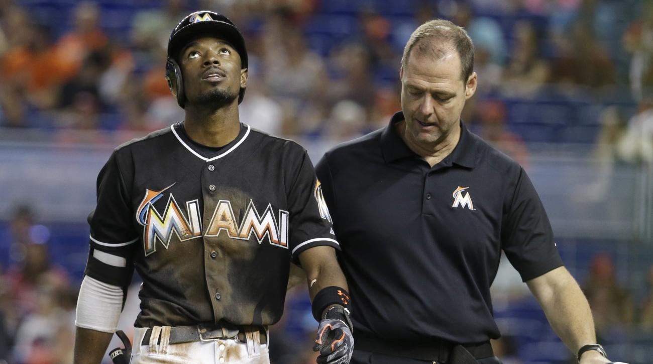 Miami Marlins' Dee Gordon, left, walks off the field with head trainer Sean Cunningham, right, after sliding safely into first in seventh inning of a baseball game against the Cincinnati Reds, Saturday, July 11, 2015, in Miami. The Marlins defeated the Re