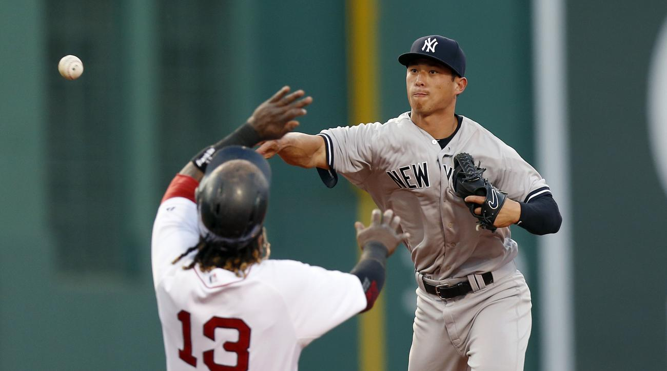Boston Red Sox's Hanley Ramirez is forced out at second base as New York Yankees' Rob Refsnyder turns the double play on Mike Napoli during the second inning of a baseball game in Boston, Saturday, July 11, 2015. (AP Photo/Michael Dwyer)