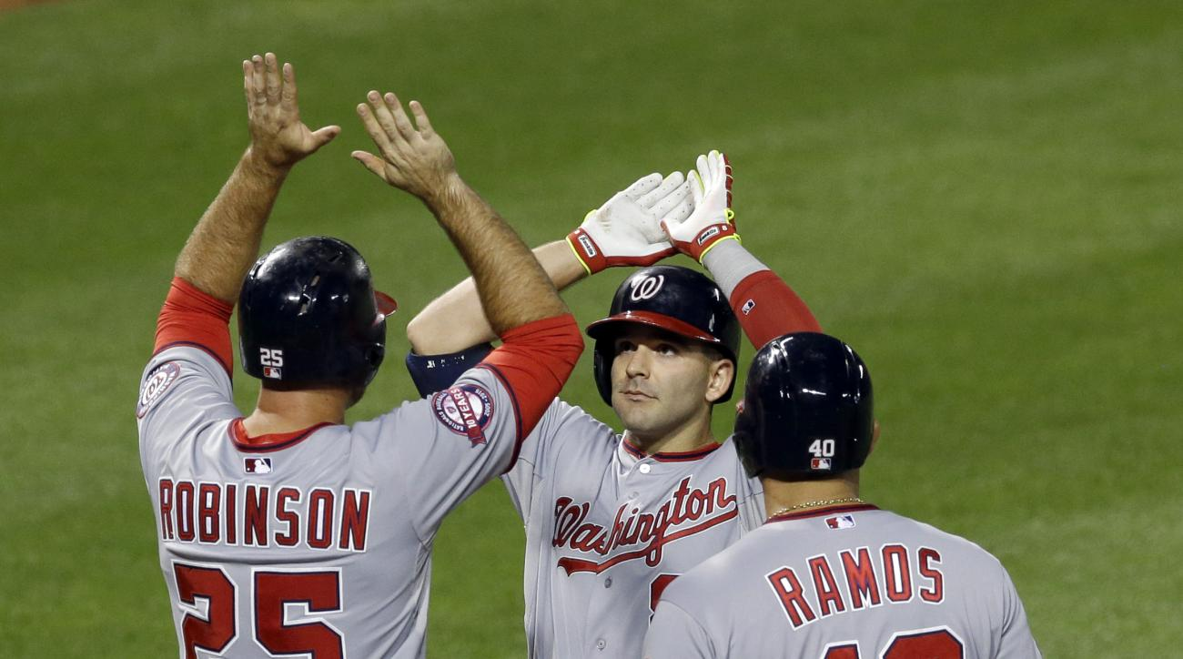 Washington Nationals' Danny Espinosa, center, high-fives teammates Clint Robinson, left, and Wilson Ramos after batting them in on a home run in the sixth inning of an interleague baseball game against the Baltimore Orioles, Saturday, July 11, 2015, in Ba