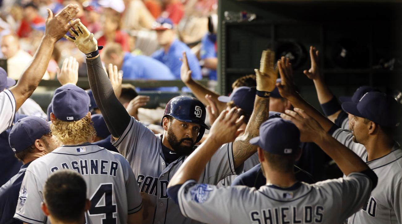 San Diego Padres' Matt Kemp, center, is congratulated by James Shields (33) and others in the dugout after Kemp hit a two-run home run off of Texas Rangers' Colby Lewis during the third inning of an interleague baseball game Saturday, July 11, 2015, in Ar