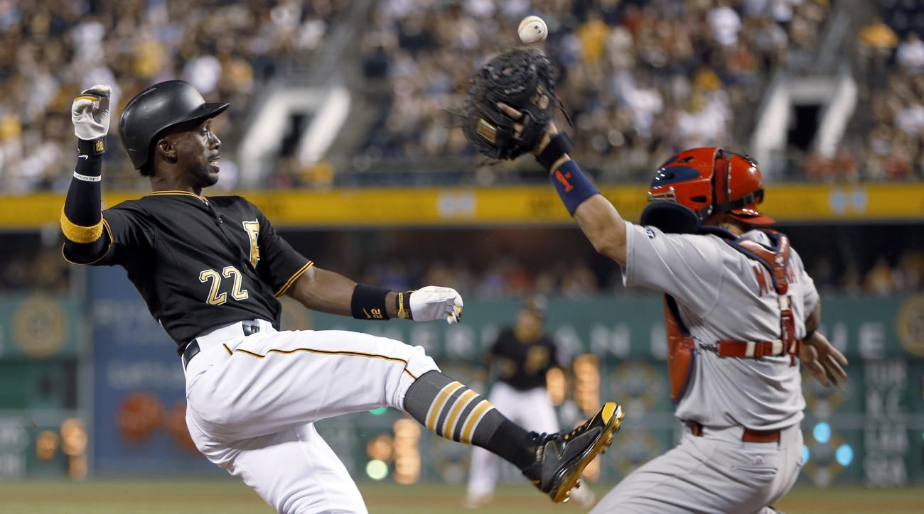 Pittsburgh Pirates' Andrew McCutchen (22) scores from second base on a hit by Jung Ho Kang as the ball gets away from St. Louis Cardinals catcher Yadier Molina during the eighth inning of a baseball game, Saturday, July 11, 2015, in Pittsburgh. (AP Photo/