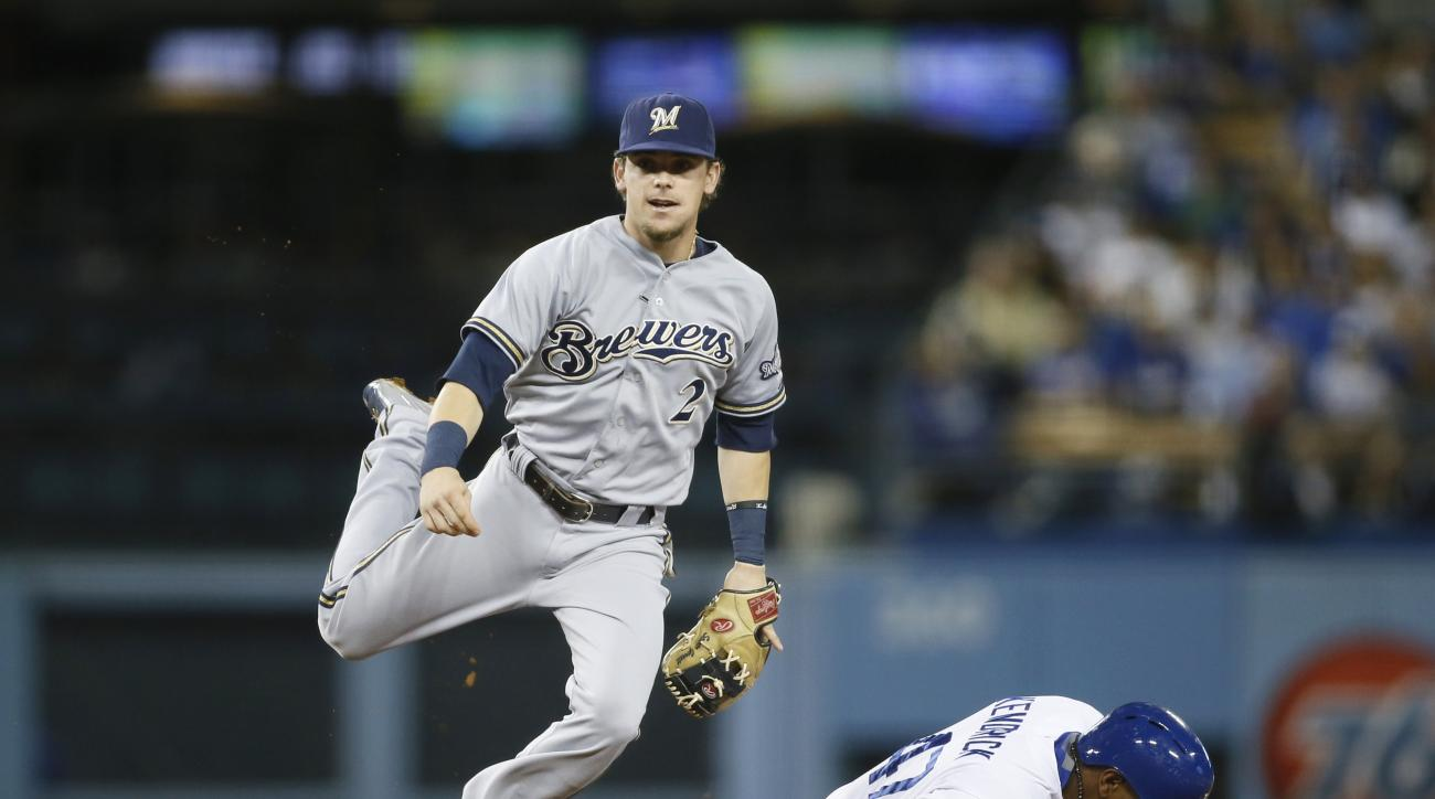 Milwaukee Brewers second baseman Scooter Gennett jumps to avoid Los Angeles Dodgers' Howie Kendrick as he completes a double play by throwing out Justin Turner at first during the fourth inning of a baseball game, Saturday, July 11, 2015, in Los Angeles.