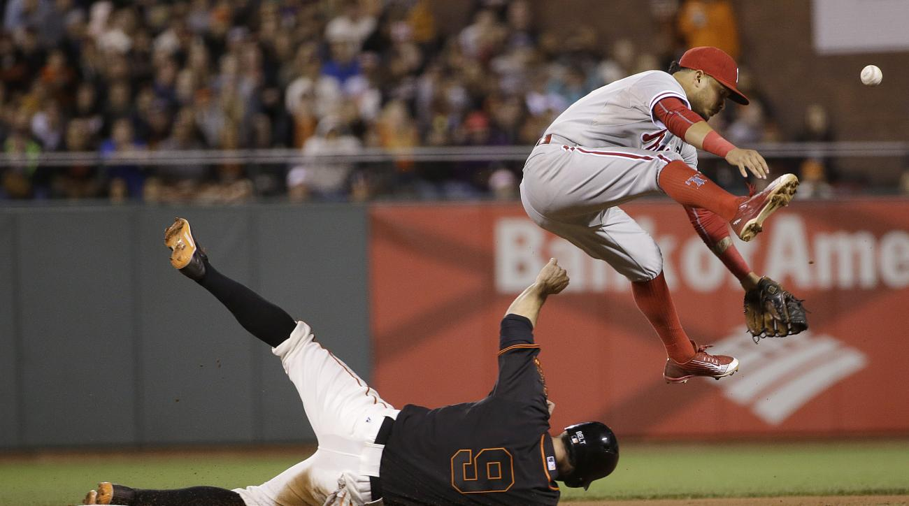 Philadelphia Phillies shortstop Freddy Galvis, top, loses the ball after forcing out San Francisco Giants' Brandon Belt (9) at second base on a ball hit by Brandon Crawford during the seventh inning of a baseball game in San Francisco, Saturday, July 11,