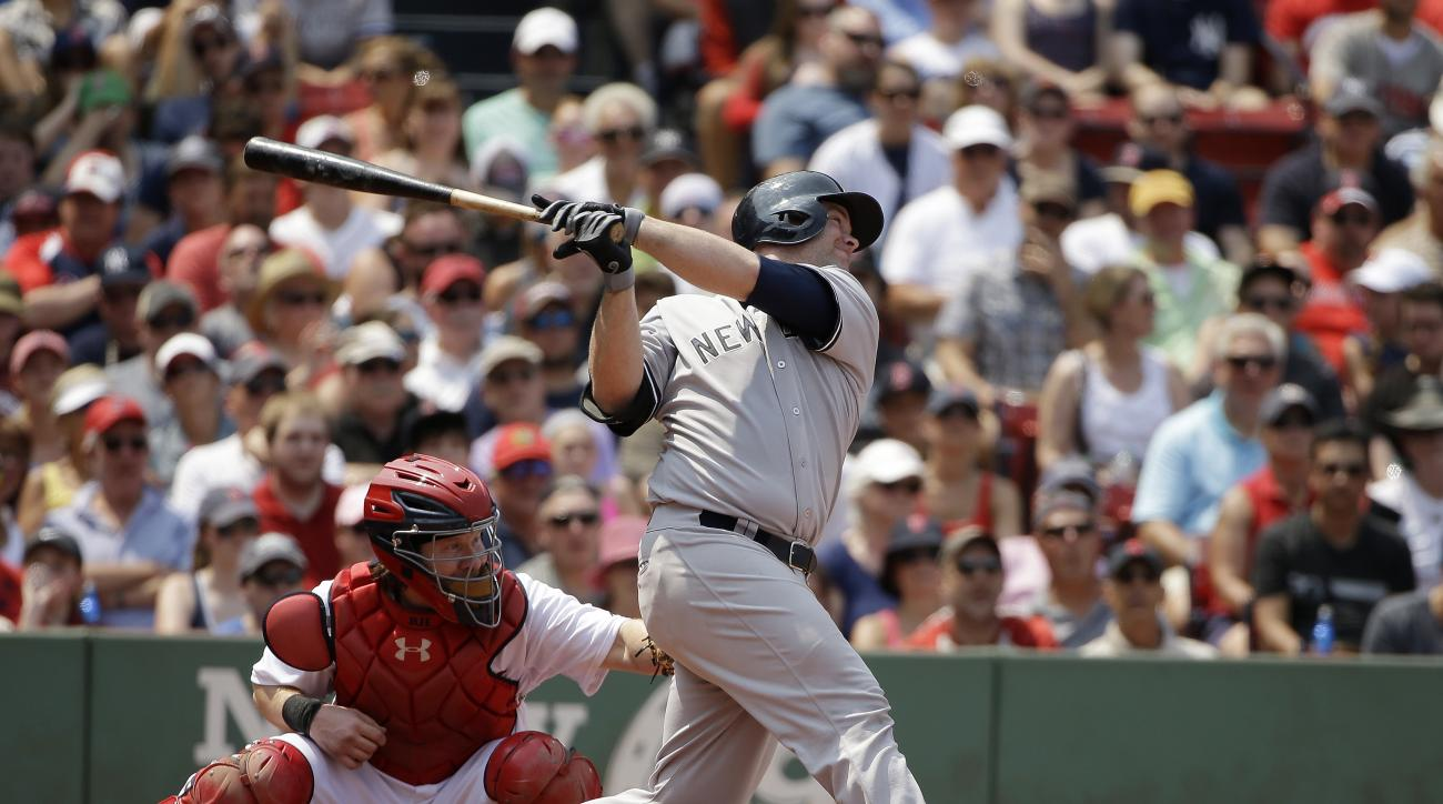 New York Yankees Brian McCann, right, hits a two-run home run as Boston Red Sox catcher Ryan Hanigan, left, looks on in the second inning of a baseball game at Fenway Park, Sunday, July 12, 2015, in Boston. (AP Photo/Steven Senne)