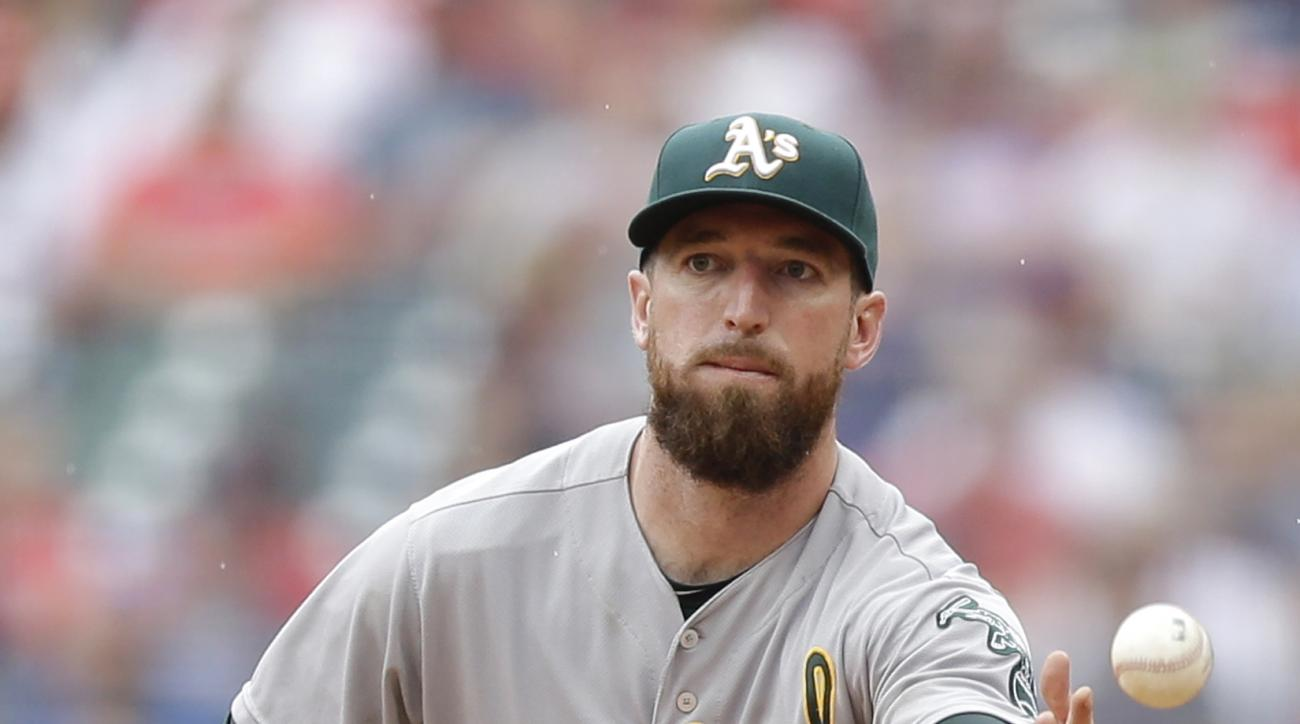 Oakland Athletics' Ike Davis tosses the ball to starting pitcher Sonny Gray to get Cleveland Indians' Jason Kipnis out at first base in the fourth inning of a baseball game, Sunday, July 12, 2015, in Cleveland. (AP Photo/Tony Dejak)