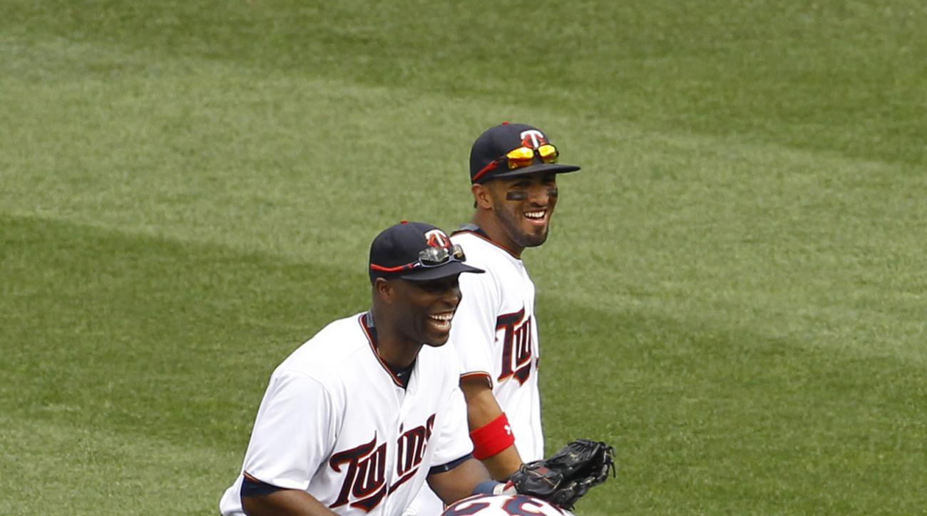 Minnesota Twins right fielder Torii Hunter, left, and left fielder Eddie Rosario, right, share a laugh after a failed celebration leap with center fielder Aaron Hicks (32) after the Twins defeated the Detroit Tigers 7-1 in a baseball game in Minneapolis,