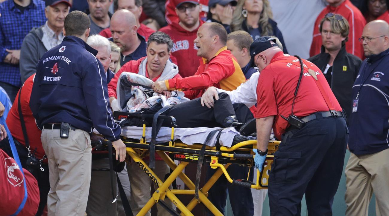 FILE - In this Friday, June 5, 2015, file photo, a fan, who was accidentally hit in the head with a broken bat by Oakland Athletics' Brett Lawrie, is helped from the stands during a baseball game against the Boston Red Sox at Fenway Park in Boston. A fede
