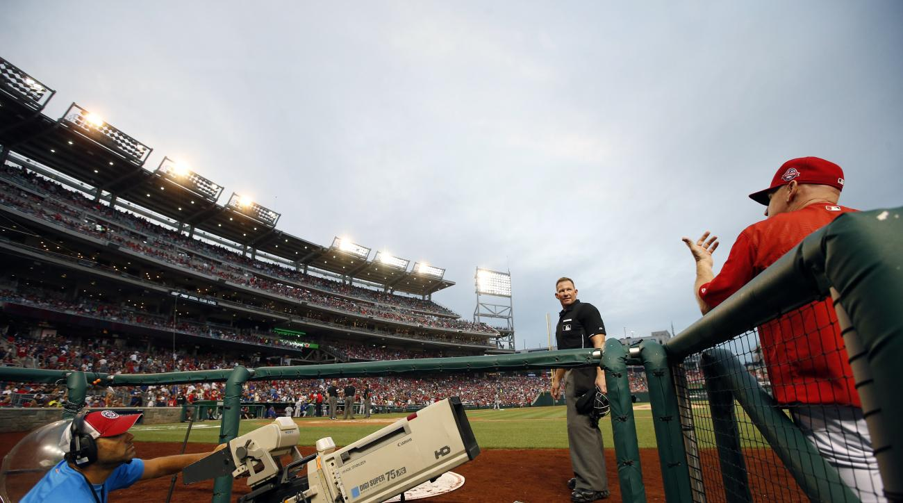 Home plate umpire Jim Wolf (28) talks with Washington Nationals manager Matt Williams (9) after some of the lights went out and play was halted during the fourth inning of a baseball game against the Los Angeles Dodgers at Nationals Park, Friday, July 17,