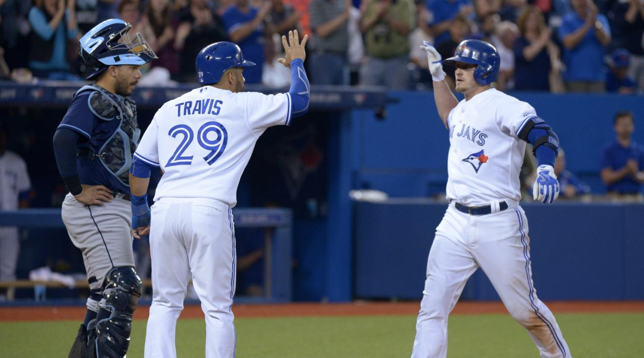 Toronto Blue Jays Josh Donaldson, right, celebrates his two-run home run with teammate Devon Travis during the fifth inning of a baseball game against the Tampa Bay Rays, Friday, July 17, 2015, in Toronto. (Jon Blacker/The Canadian Press via AP) MANDATORY
