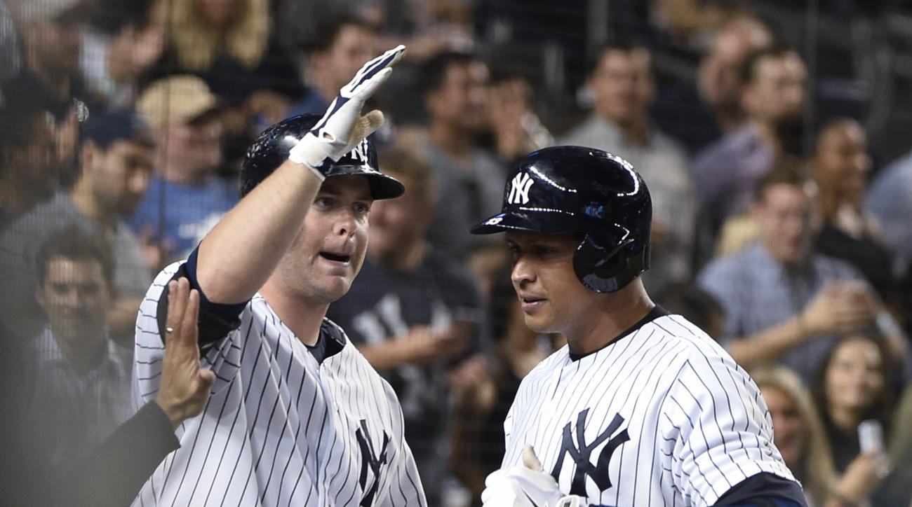 New York Yankees' Brian McCann, left, greets Alex Rodriguez at the dugout after Rodriguez hit a solo home run off Seattle Mariners relief pitcher Joe Beimel during the seventh inning of a baseball game at Yankee Stadium on Friday, July 17, 2015, in New Yo