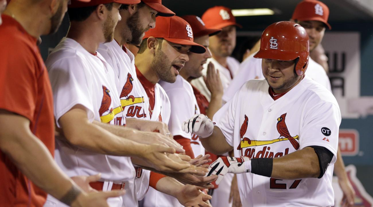 St. Louis Cardinals' Jhonny Peralta (27) is congratulated by teammates in the dugout after hitting a solo home run during the sixth inning of a baseball game against the New York Mets, Friday, July 17, 2015, in St. Louis. (AP Photo/Jeff Roberson)