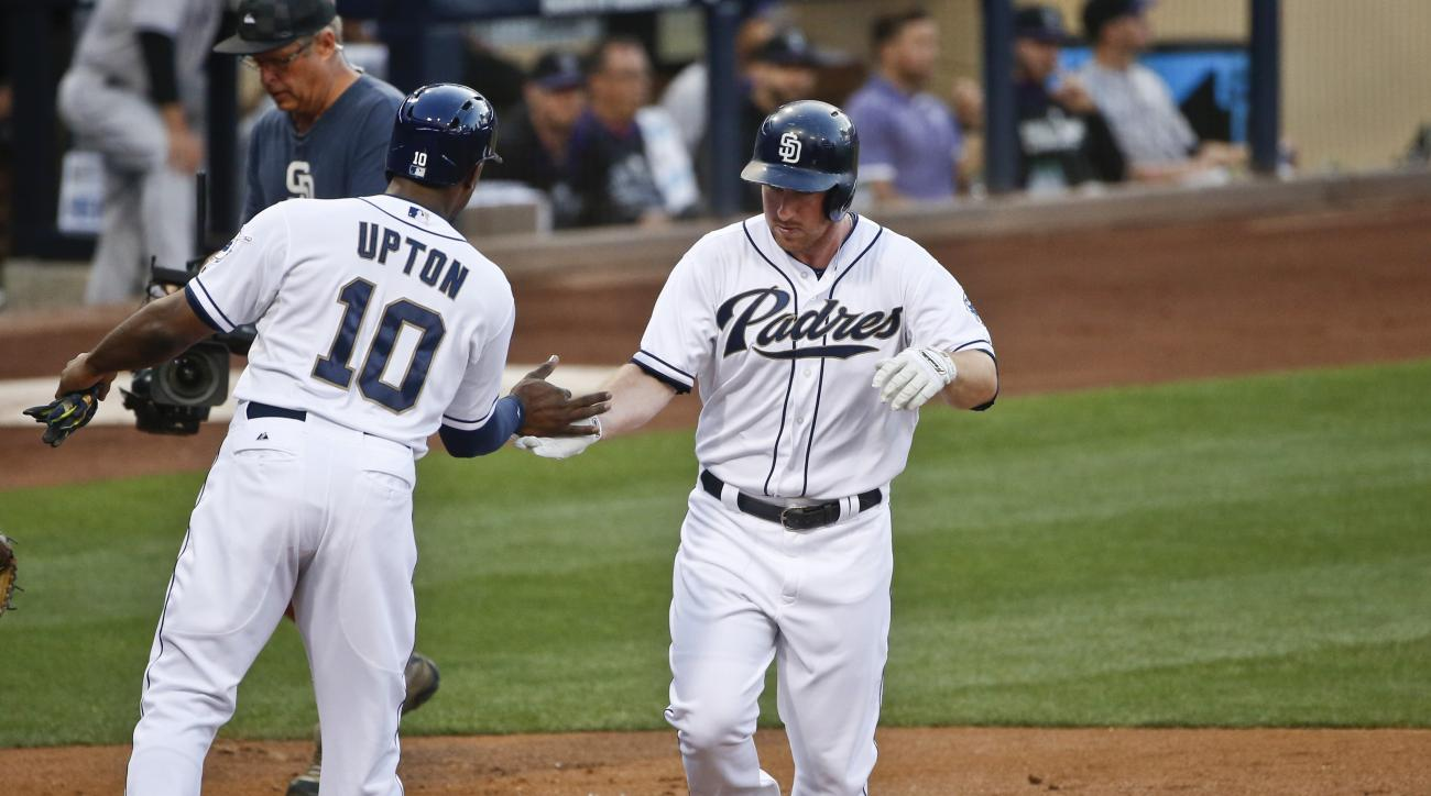 San Diego Padres' Jedd Gyorko is congratulated by Justin Upton after hitting a two-run home run during the first inning of a baseball game against the Colorado Rockies on Friday, July 17, 2015, in San Diego. (AP Photo/Lenny Ignelzi)